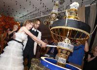 Молодые режут свадебный торт в виде люстры