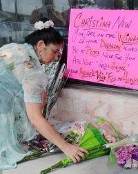 Люди несут к месту убийства певицы цветы